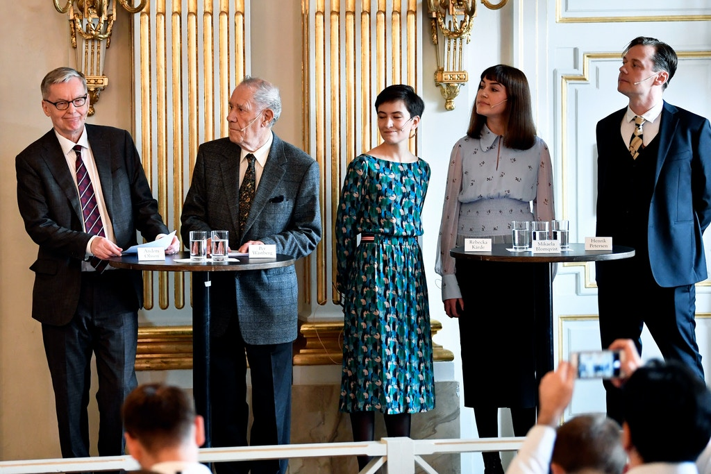 Members of the Swedish Academy, from left, Anders Olsson, Par Westberg, Rebecka Karde, Mikael Blomqvist and Henrik Petersen after the announcement of the winners of the 2018 and 2019 Nobel Prize in Literature, in Stockholm, Sweden, Thursday Oct. 10, 2019. The 2018 Nobel Prize in literature has been awarded to Polish author Olga Tokarczuk, while the 2019 prize went to Austrian author Peter Handke. (Anders Wiklund/TT via AP)