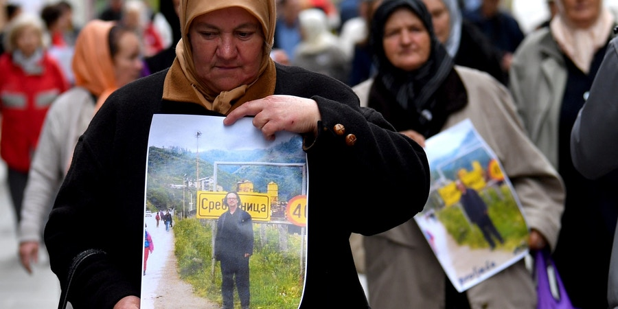 Women from Srebrenica and Bosnian members of associations of survivors of the war in Bosnia (1992 - 1995), hold placards depicting Austrian writter Peter Handke as they take part in a demonstration in front of the Swedish Embassy in Sarajevo, on November 5, 2019, to protest against Nobel literature prize laureate Handke, whom they accuse of being a Serb apologist during the 1990s wars. - Demonstrators hold photos of the writer while he was on a personal visit to their hometown of Srebrenica, where some 8,000 Bosnian Muslim men and boys were slaughtered by Bosnian Serb forces in July 1995. The photo shows the novelist standing in front of a sign at the entrance of the town allegedly in 1996, according to the women protesting. The Swedish academy's pick last month trigged outrage in the Balkans and beyond because of Handke's admiration for late Serbian strongman Slobodan Milosevic. (Photo by ELVIS BARUKCIC / AFP) (Photo by ELVIS BARUKCIC/AFP via Getty Images)