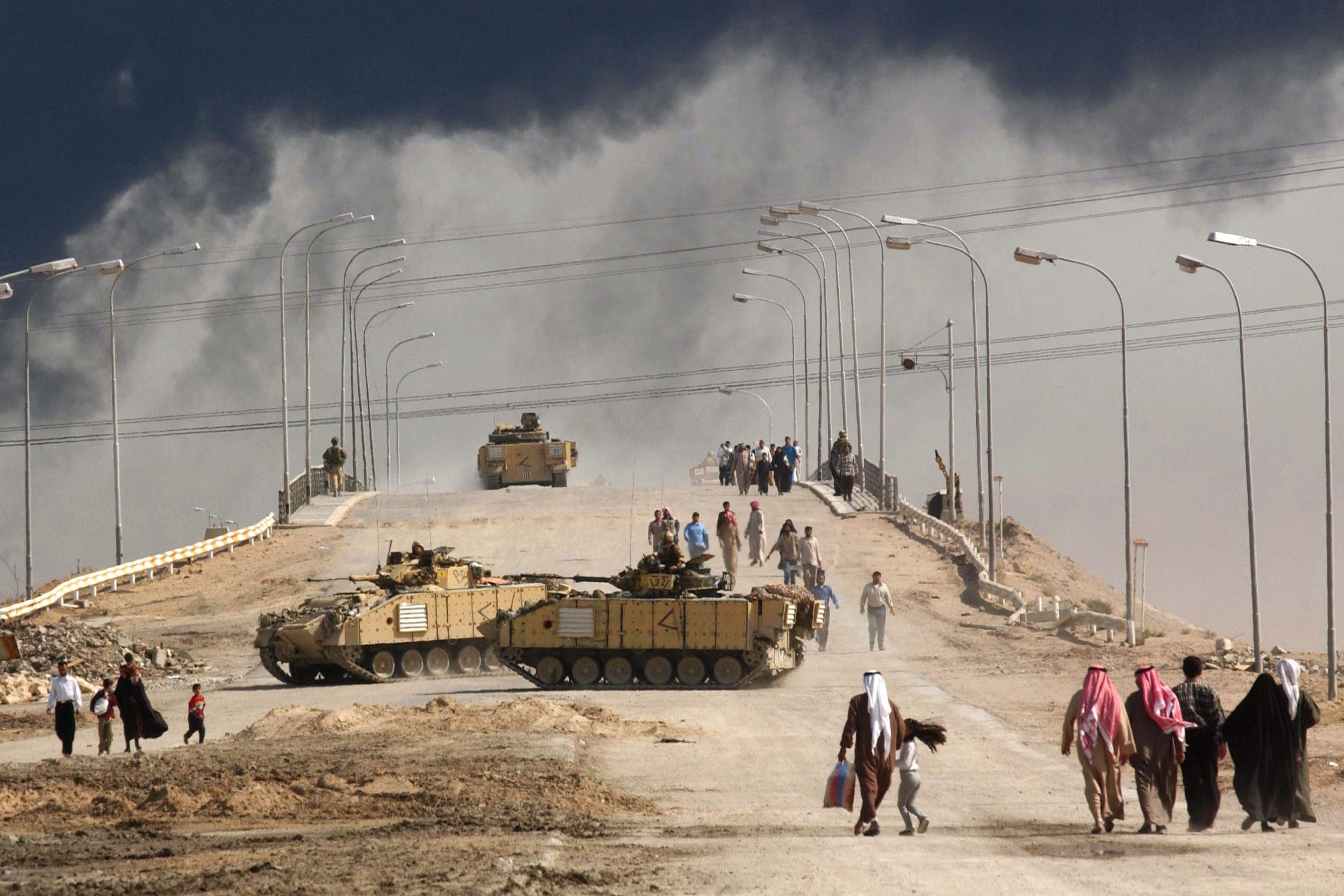 BASRA, IRAQ - MARCH 29:  Civilians on foot pass tanks on a bridge near the entrance to the besieged city of Basra March 29, 2003 in Iraq. Baath Party loyalists have taken up positions in Basra, Iraq's second largest city, making it a target of the U.S.-led war on Iraq.  (Photo by Spencer Platt/Getty Images)