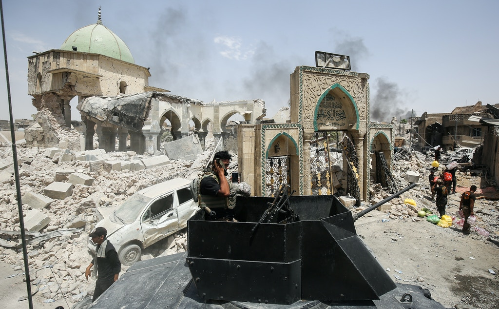 A member of the Iraqi Counter-Terrorism Service (CTS) wipes his face while standing in the turret of a humvee parked outside the destroyed gate of Al-Nuri Mosque in the Old City of Mosul on July 2, 2017, during the offensive to retake the city from Islamic State (IS) group fighters. Explosions on the evening of June 21, 2017 levelled the mosque where Abu Bakr al-Baghdadi gave his first sermon as leader of the Islamic State group, along with its ancient minaret. / AFP PHOTO / AHMAD AL-RUBAYE        (Photo credit should read AHMAD AL-RUBAYE/AFP via Getty Images)