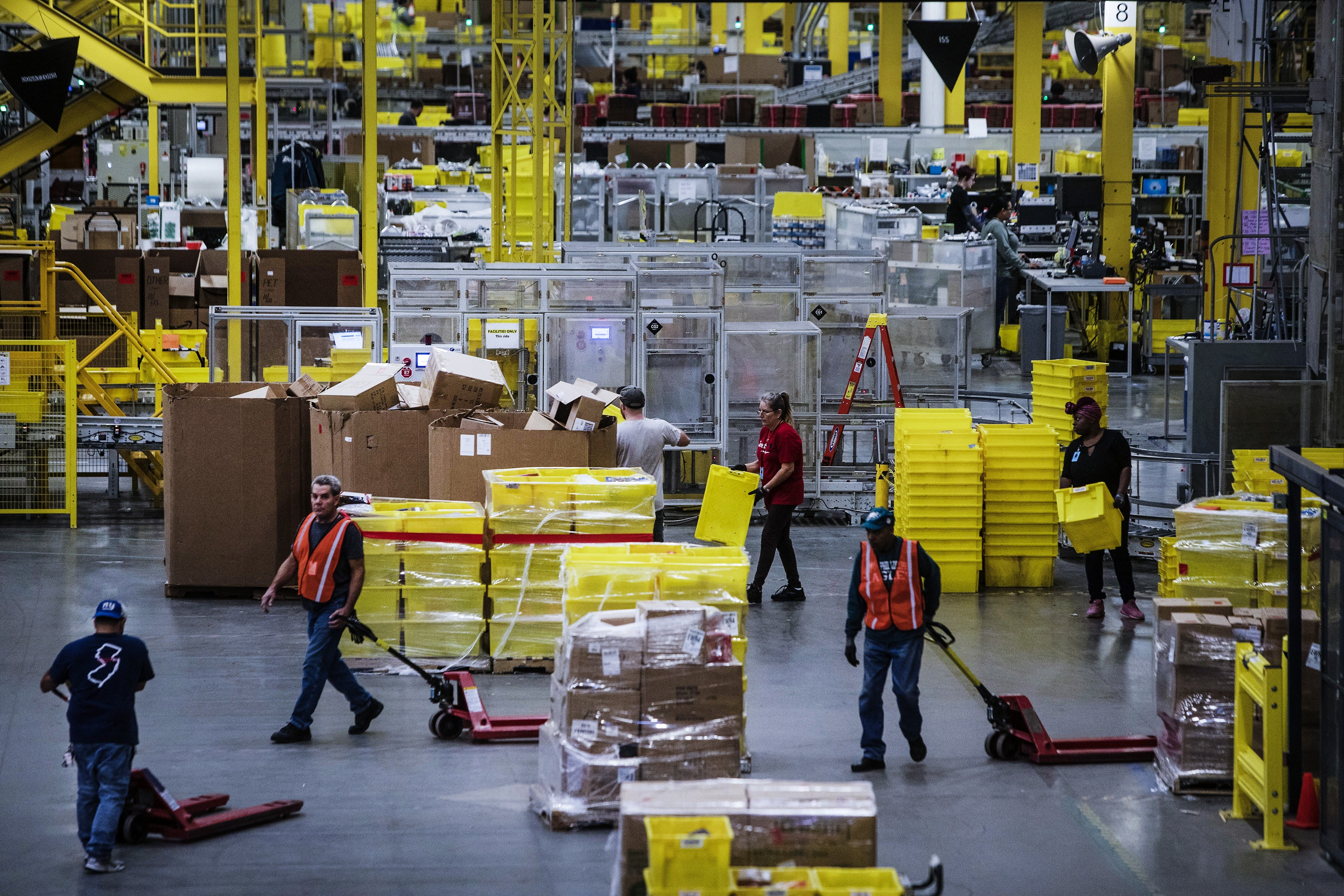 Employees pull pallet trucks at the Amazon.com Inc. fulfillment center in Robbinsville, New Jersey, U.S., on Monday, Nov. 27, 2017. The holiday shopping season is off to a strong start and retailers appear to be continuing the momentum today -- Cyber Monday -- the biggest online spending day of the year. Photographer: Victor J. Blue/Bloomberg via Getty Images