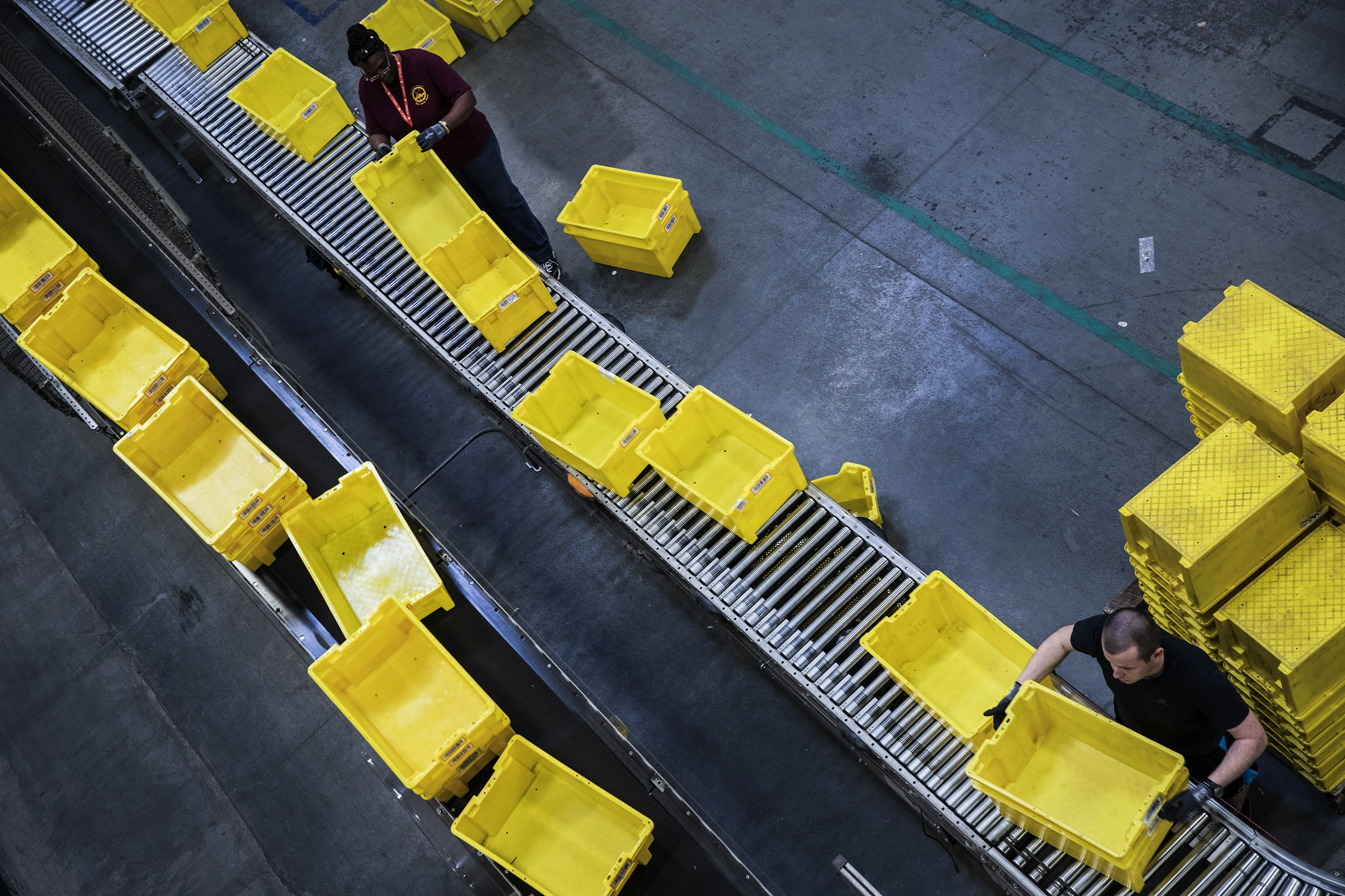Employees organize plastic bins for orders at the Amazon.com Inc. fulfillment center in Robbinsville, New Jersey, U.S., on Monday, Nov. 27, 2017. The holiday shopping season is off to a strong start and retailers appear to be continuing the momentum today -- Cyber Monday -- the biggest online spending day of the year. Photographer: Victor J. Blue/Bloomberg via Getty Images