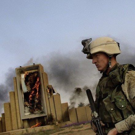 IRAQ. Baghdad. A US Marine in front of a burning poster of Saddam Hussein. April 10 2003.
