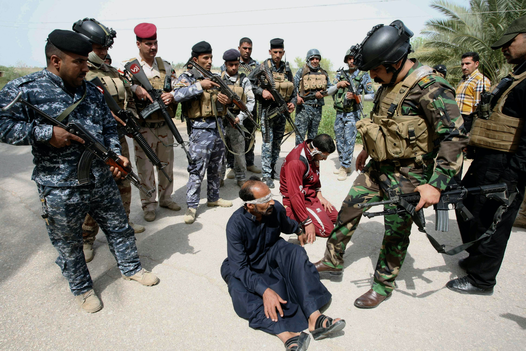 Personnel from the Iraqi security forces arrest suspected militants of the al Qaeda-linked Islamic State in Iraq and the Levant (ISIL), during clashes with Iraqi security forces in Jurf al-Sakhar March 17, 2014.   REUTERS/Alaa Al-Marjani (IRAQ - Tags - Tags: CIVIL UNREST CRIME LAW MILITARY) - GM1EA3I0G4Q01
