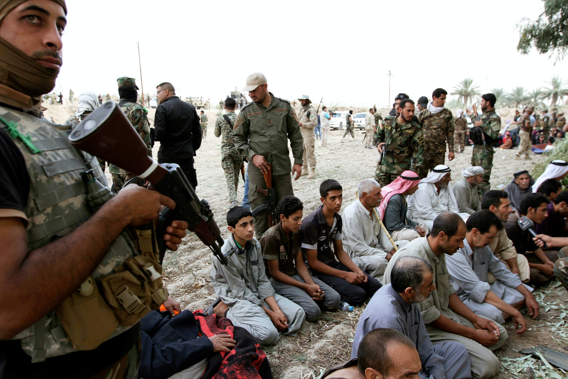 Iraqi families sit after surrendering to Shi'ite fighters and Iraqi Army after they took control of Jurf al-Sakhar from Islamist State militants, October 27, 2014. The families, who were in militant-held areas, surrendered to the army to be transported to safe areas and escape clashes between militants and Iraqi security forces, according to the Iraqi Army and the fighters. Picture taken October 27, 2014. REUTERS/Mahmoud Raouf Mahmoud (IRAQ - Tags: CIVIL UNREST POLITICS CONFLICT MILITARY SOCIETY TPX IMAGES OF THE DAY) - GM1EAAS1L0D01