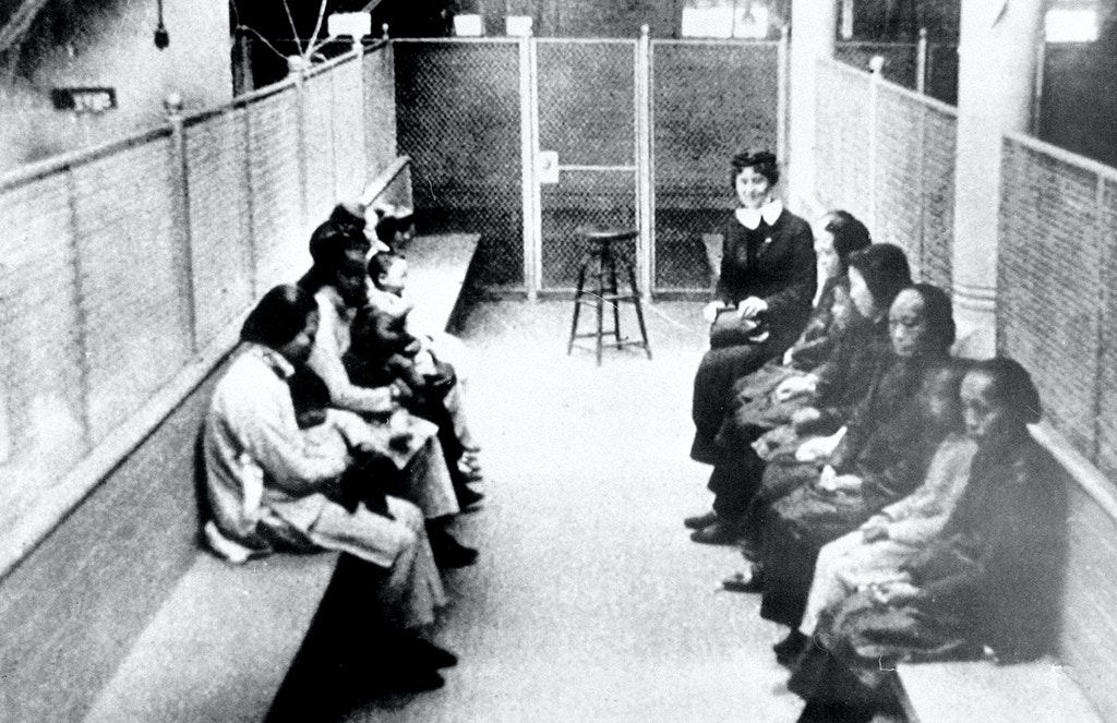 A group of Chinese and Japanese women and children wait to be processed as they are held in a wire mesh enclosure at the Angel Island Internment barracks in San Francisco Bay in the late 1920s.  The Angel Island Immigration Station processed one million immigrants from 1910 to 1940, mostly from China and Japan.  (AP Photo)