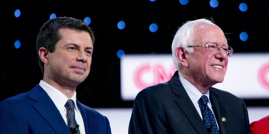 2020 Democratic Presidential Candidates Pete Buttigieg, mayor of South Bend, left to right, Senator Bernie Sanders, an independent from Vermont, and Senator Elizabeth Warren, a Democrat from Massachusetts, stand on stage during the Democratic presidential candidate debate in Detroit, Michigan, U.S., on Tuesday, July 30, 2019. The question of what it will take to defeat President Donald Trump next year took center stage at the Democratic debate as moderate rivals to Warren and Sanders argued their promises of sweeping, fundamental change are unrealistic and will drive voters to the GOP. Photographer: Anthony Lanzilote/Bloomberg via Getty Images