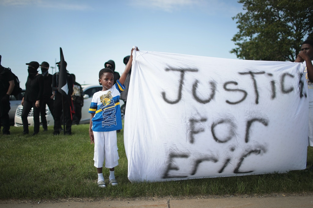 "SOUTH BEND, INDIANA - JUNE 29: Demonstrators protest the shooting death of Eric Logan outside of the South Bend Police Station following his funeral on June 29, 2019 in South Bend, Indiana. Logan was shot and killed by South Bend Police Sgt. Ryan O'Neill who was investigating a report of car break-ins in the area. Logan was reported to be holding a knife when he was shot. The shooting caused outrage in the community and turmoil for Democratic presidential candidate Pete Buttigieg who is mayor of the city. ""It's a mess"" said Buttigieg referring to the shooting during the presidential debate in Miami on Thursday. (Photo by Scott Olson/Getty Images)"