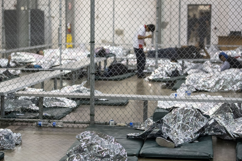 MCALLEN, TEXAS - AUGUST 12:Male minors rest under mylar blankets in the US Border Patrol Central Processing Center in McAllen, Texas on August 12, 2019. Border Patrol officials said that 1,267 people were being held and processed in the facility at the time of the tour. Some of the minors are unaccompanied and others crossed with their families, but after a certain age are held in a separate area within the same building as their parents. (Photo by Carolyn Van Houten/The Washington Post via Getty Images)