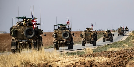 A convoy of US armoured vehicles patrols the northeastern town of Qahtaniyah at the border with Turkey, on October 31, 2019. - US forces accompanied by Kurdish fighters of the Syrian Democratic Forces (SDF) patrolled part of Syria's border with Turkey, in the first such move since Washington withdrew troops from the area earlier this month, an AFP correspondent reported. (Photo by Delil SOULEIMAN / AFP) (Photo by DELIL SOULEIMAN/AFP via Getty Images)
