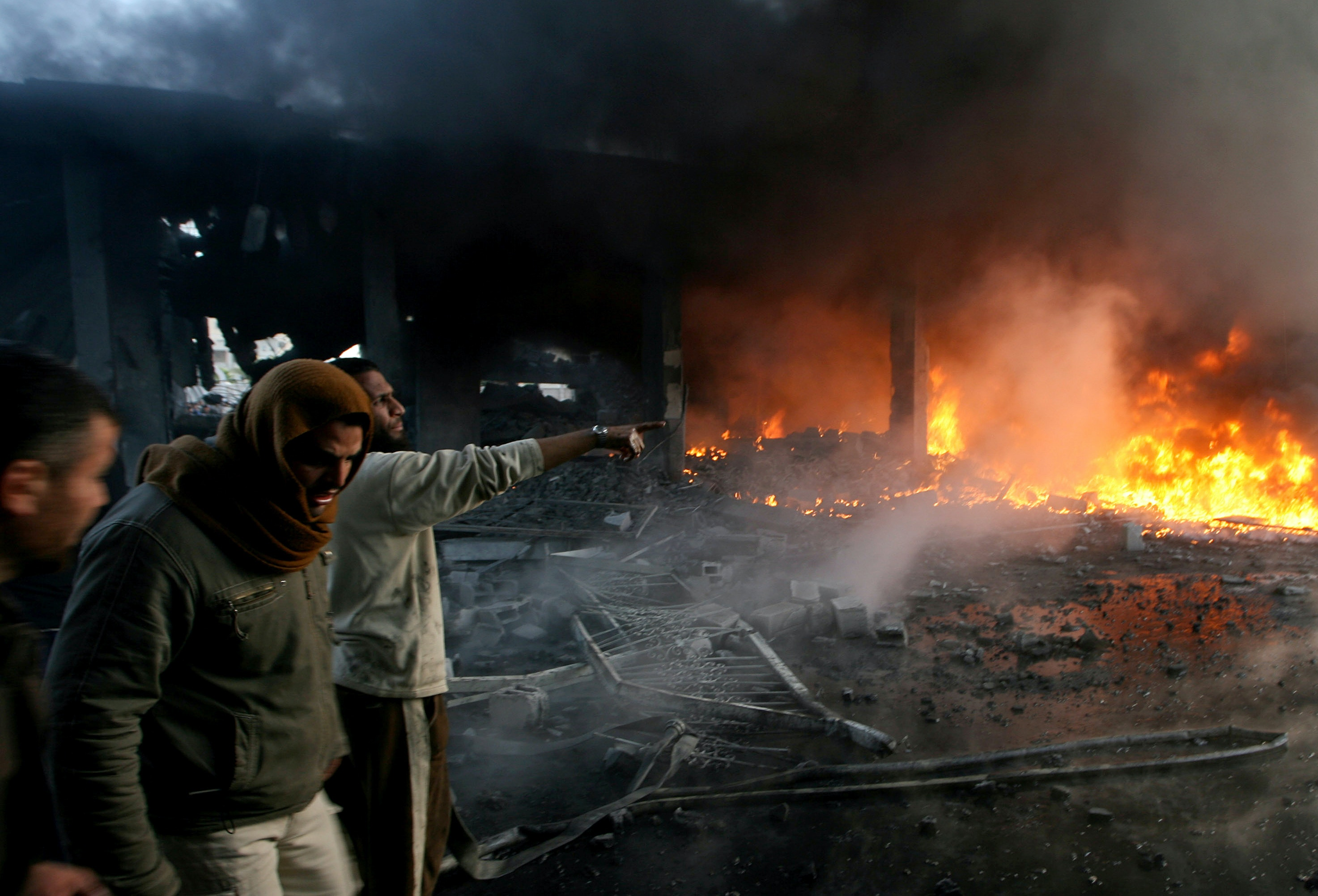 RAFAH, GAZA STRIP - DECEMBER 28:  Palestinian men look on as flames rise from debris at the site of an Israeli air strike on December 28, 2008 in Rafah, Gaza. Israel has launched further air strikes with more than 200 Palestinians reportedly killed and hundreds more wounded, in an effort to end Palestinian rocket attacks against Israeli civilian targets. (Photo Getty Images)
