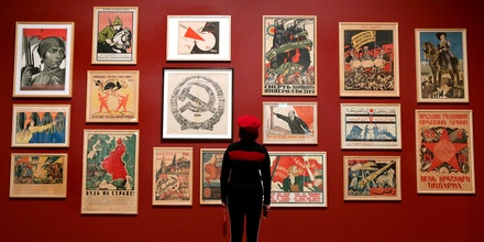 A visitor poses in front of a mural with various posters including:  artist Adolf Strakhov's 'Emancipated Woman: Build socialism!' c. 1926 (top-L) and artist Valentin Shcherbakov's 'A Spectre is Haunting Europe, the Spectre of Communism' c. 1924, during the 'Red Star over Russia: A revolution in Visual Culture 1905-55' exhibition at the Tate Modern in London on November 7, 2017. / AFP PHOTO / Daniel LEAL-OLIVAS / RESTRICTED TO EDITORIAL USE - MANDATORY MENTION OF THE ARTIST UPON PUBLICATION - TO ILLUSTRATE THE EVENT AS SPECIFIED IN THE CAPTION        (Photo credit should read DANIEL LEAL-OLIVAS/AFP via Getty Images)