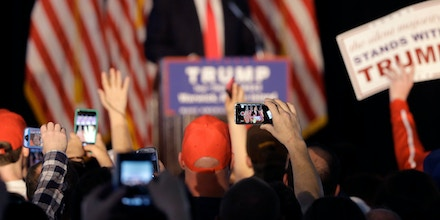 People in the audience use mobile phones to record Republican presidential candidate Donald Trump, behind, as he addresses an audience during a campaign rally, Monday, April 25, 2016, in Warwick, R.I. (AP Photo/Steven Senne)