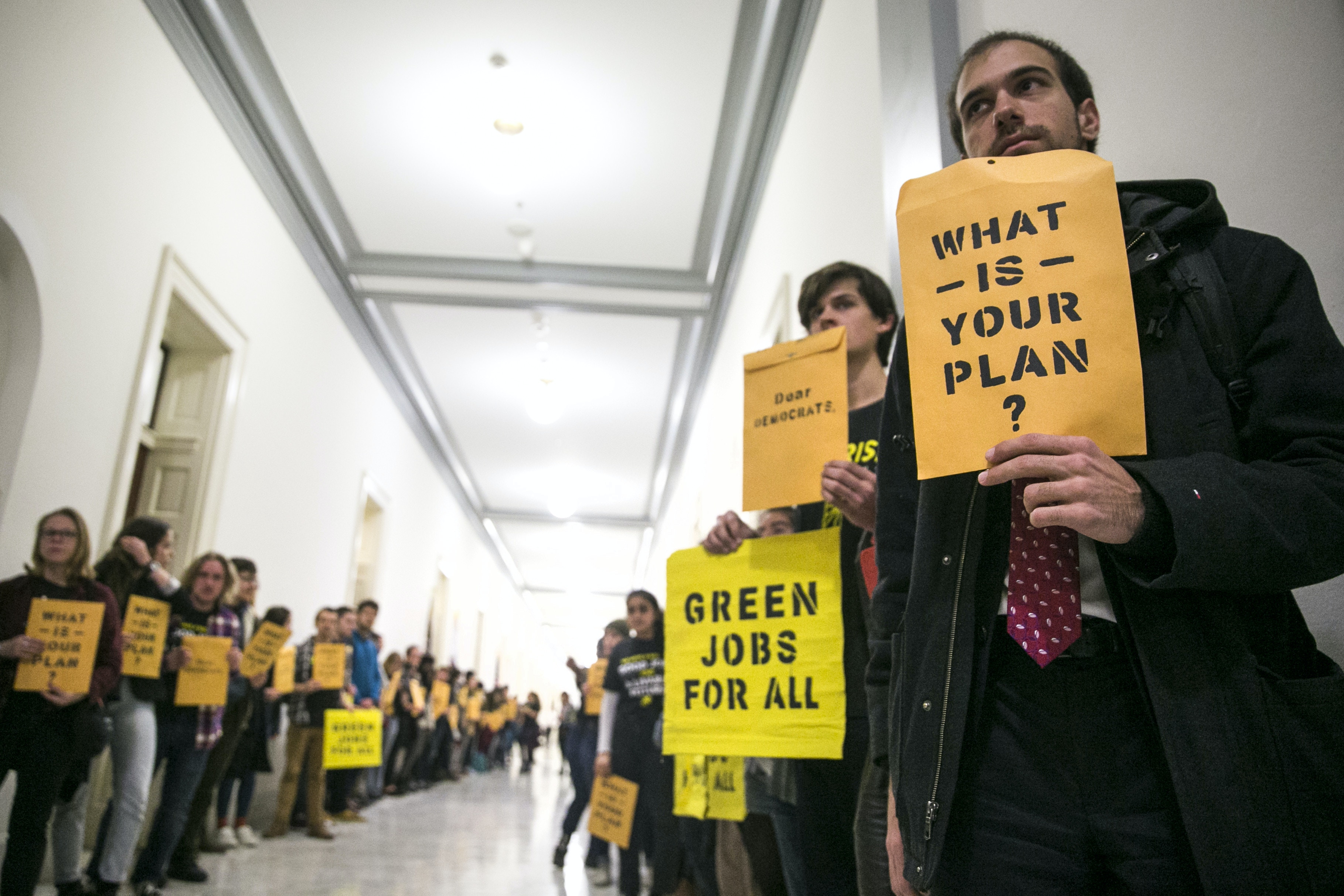 Protesters from the Sunrise Movement gather outside the offices of House Minority Leader Nancy Pelosi (D-Calif.) on Capitol Hill, in Washington, Nov. 13, 2018. Alexandria Ocasio-Cortez, congresswoman-elect from New York, also made a visit to the protest. (Sarah Silbiger/The New York Times)