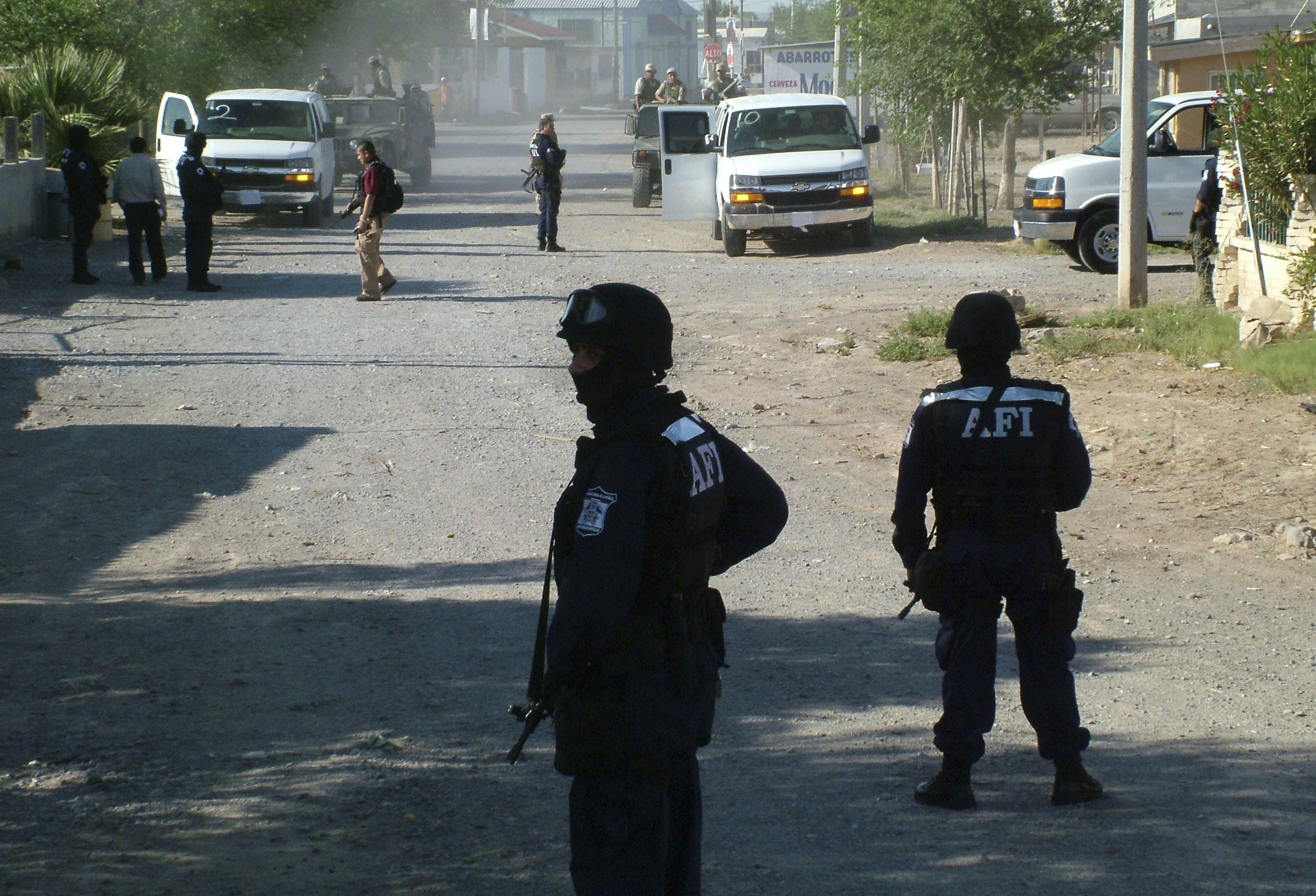 Members of Mexico's Federal Investigation agency, AFI, as well as Mexican army soldiers guard a street during a raid  to search for members of the Juarez drug cartel on the outskirts of Ciudad Juarez, Mexico on Wednesday June 14, 2006. Mexico's drug wars are becoming a central issue in the country's July 2 presidential race, with one candidate calling for U.S.-style trials and extraditions and another saying crime can only be solved with more jobs and social programs.(AP Photo/Raymundo Ruiz)