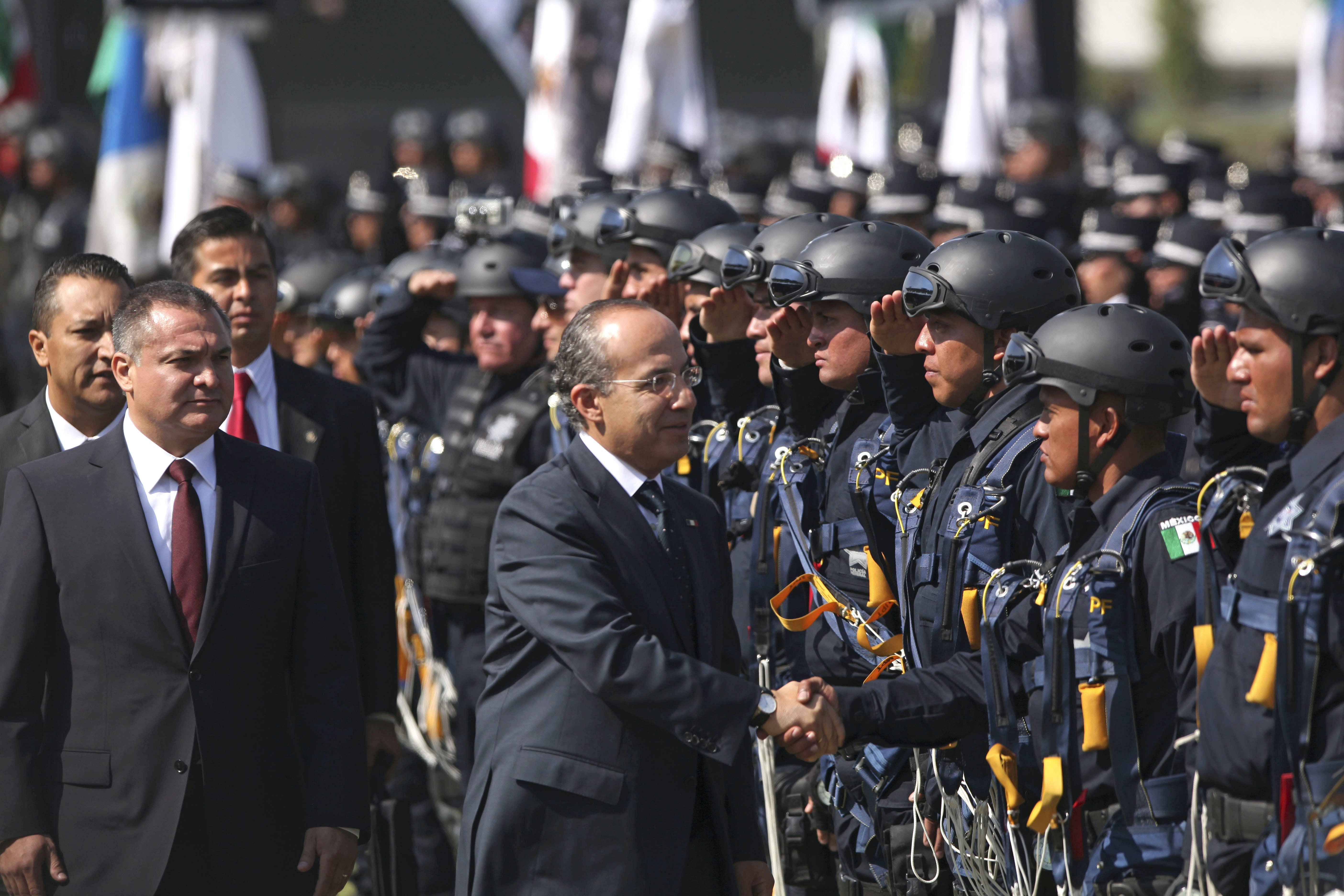 Mexico's President Felipe Calderon, center, followed by Mexico's Public Safety Secretary Genaro Garcia Luna, left, shakes hands with Federal Police officers during a ceremony to designate June 2 as the Federal Police Day in Mexico City, Thursday, June 2, 2011. (AP Photo/Alexandre Meneghini)