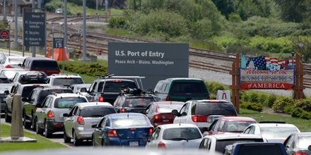 In this photo taken Thursday, May 23, 2013, cars from Canada line up to cross into the U.S. in Blaine, Wash., at Peace Arch State Park. (AP Photo/Elaine Thompson)