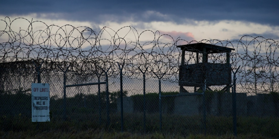In this photo reviewed by U.S. military officials, the sun sets behind the closed Camp X-Ray detention facility, Wednesday, April 17, 2019, in Guantanamo Bay Naval Base, Cuba. (AP Photo/Alex Brandon)