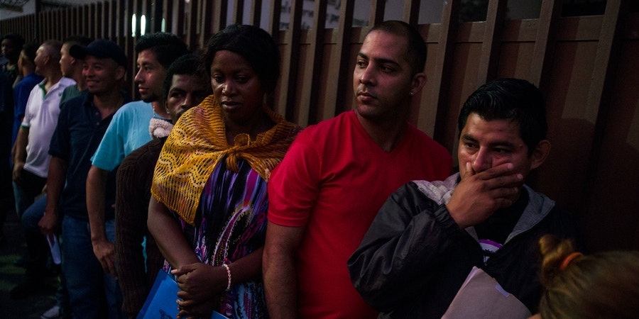 Migrants wait in line outside the Mexican Commission for Migrant Assistance office to get the documents needed that allows them to stay in Mexico, in Tapachula, Thursday, June 20, 2019. The flow of migrants into southern Mexico has seemed to slow in recent days as more soldiers, marines, federal police, many as part of Mexico's newly formed National Guard, deploy to the border under a tougher new policy adopted at a time of increased pressure from the Trump administration.  (AP Photo/Oliver de Ros)