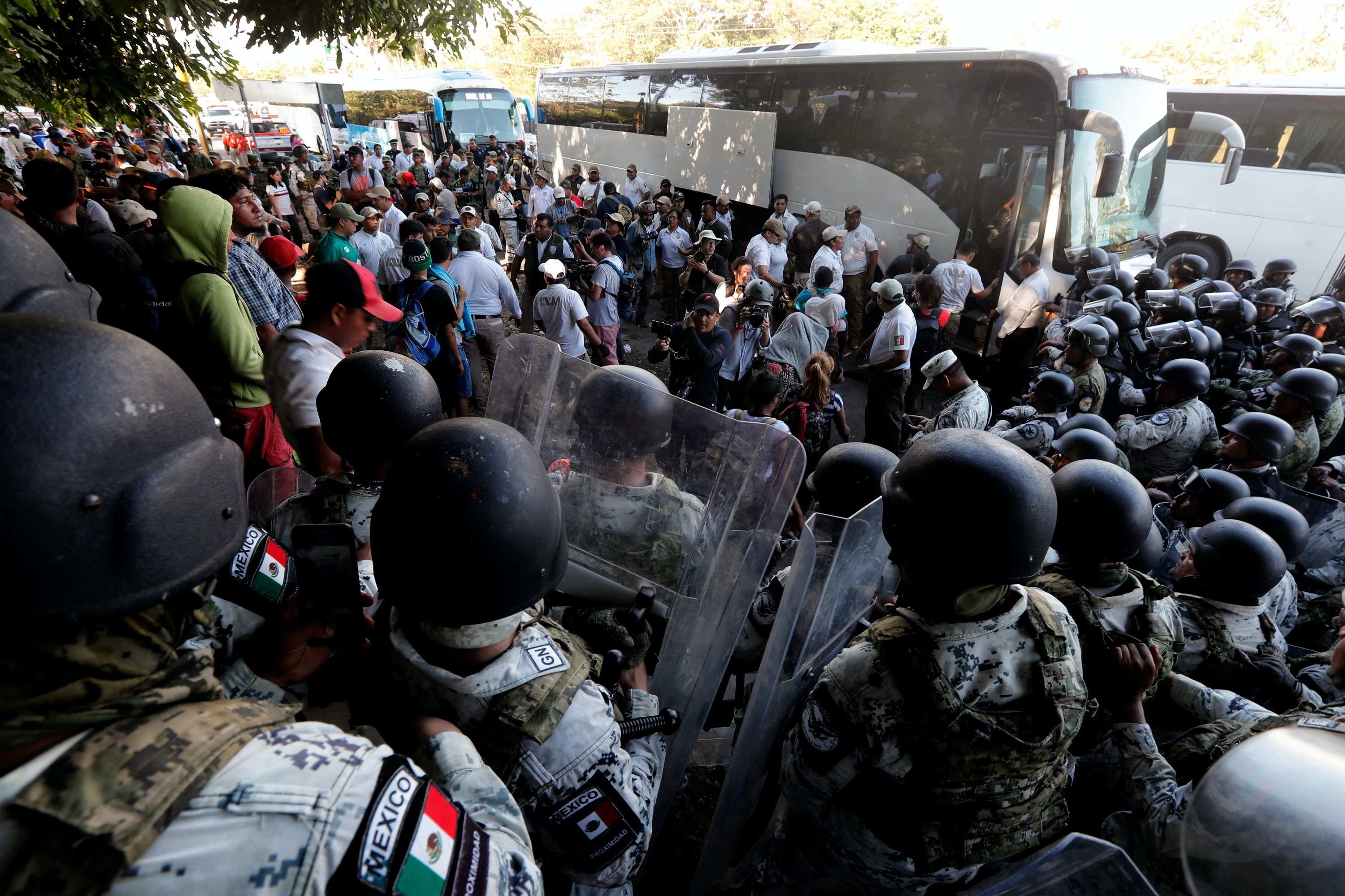 Migrants board buses after their passage was blocked by Mexican National Guards near Tapachula, Mexico, Thursday, Jan. 23, 2020. Hundreds of Central American migrants crossed the Suchiate River into Mexico from Guatemala Thursday after a days-long standoff with security forces. (AP Photo/Marco Ugarte)