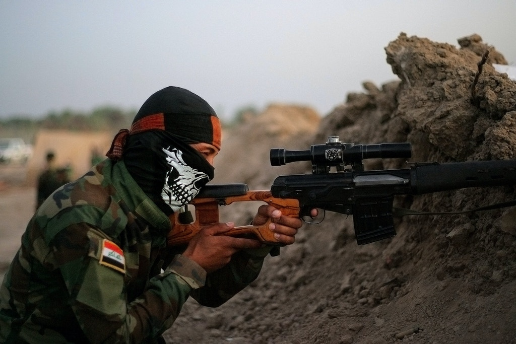 In this Sunday, Sept. 28, 2014 photo, an Iraqi Shiite militiaman aims his weapon after clashes with militants from the Islamic State group, in Jurf al-Sakhar, 43 miles (70 kilometers) south of Baghdad, Iraq. (AP Photo)