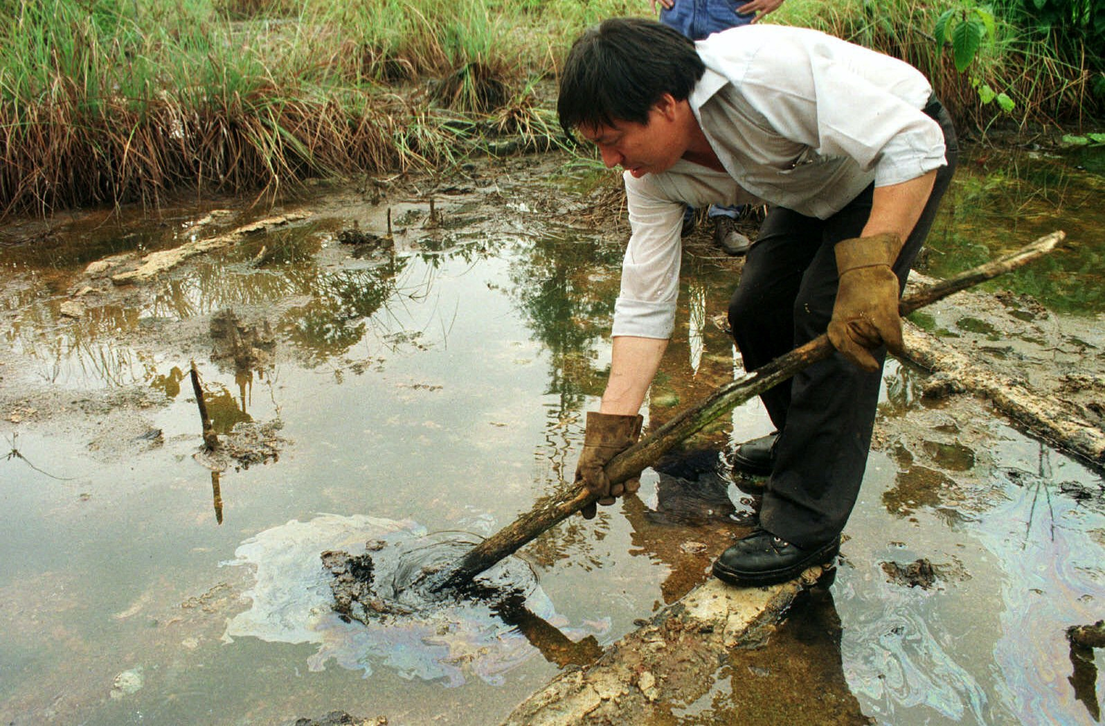"Manuel Silva a peasant  shows an oil spill in Lago Agrio,in Ecuador eastern Amazonian jungles,Monday,Dec.14,1998. Ecuadorean Indians have suited Texaco Inc.  accusing the company of turning the region's rain forests into a ""toxic waste dump"" by drilling for oil.(AP Photo/Dolores Ochoa)."