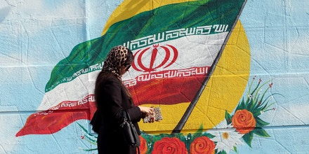 An Iranian woman walks past a mural painting of the Islamic republic's national flag in central Tehran on November 7, 2019. - Iran resumed uranium enrichment at its underground Fordow plant south of Tehran in a new step back from its commitments under a landmark 2015 nuclear deal. (Photo by STR / AFP) (Photo by STR/afp/AFP via Getty Images)