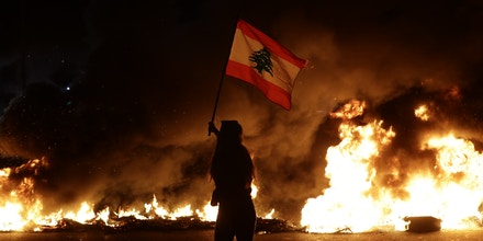 A Lebanese anti-government protester waves a Lebanese flag in front of burning tires that block the main highway linking the city of Tripoli to Beirut at the coastal city of Byblos, north of the capital on November 13, 2019. - Protesters took the streets and blocked most of the countries main roads and highways shortly after Lebanese President Michel Aoun televised interview. (Photo by Joseph EID / AFP) (Photo by JOSEPH EID/AFP via Getty Images)