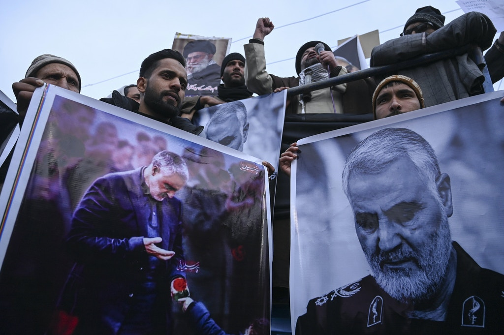 "Protesters shout slogans against the United States and Israel as they hold posters with the image of top Iranian commander Qasem Soleimani, who was killed in a US airstrike in Iraq, and Iranian President Hassan Rouhani during a demonstration in the Kashmiri town of Magam on January 3, 2020. - Hundreds of people in Indian Kashmir staged ""anti-American"" demonstrations in the troubled territory on January 3 within hours of US forces killing a top Iranian commander. (Photo by Tauseef MUSTAFA / AFP) (Photo by TAUSEEF MUSTAFA/AFP via Getty Images)"