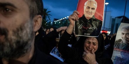 TEHRAN, IRAN - 2020/01/07: A woman crying while holding a poster of Qasem soleimani.Four days after the death of General Qasem Soleimani by the US military in Iraq, people across Iran's cities mourned and demanded a harsh revenge on the United States. (Photo by Babak Jeddi/SOPA Images/LightRocket via Getty Images)