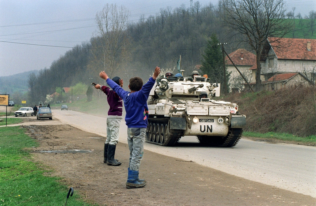 Two Bosnian boys salute a Canadian blue helmets convoy, 17 April 1993 near Tuzla, departing for the Moslem enclave of Srebrenica, where some 30000 refugees hope to be evacuated from.
