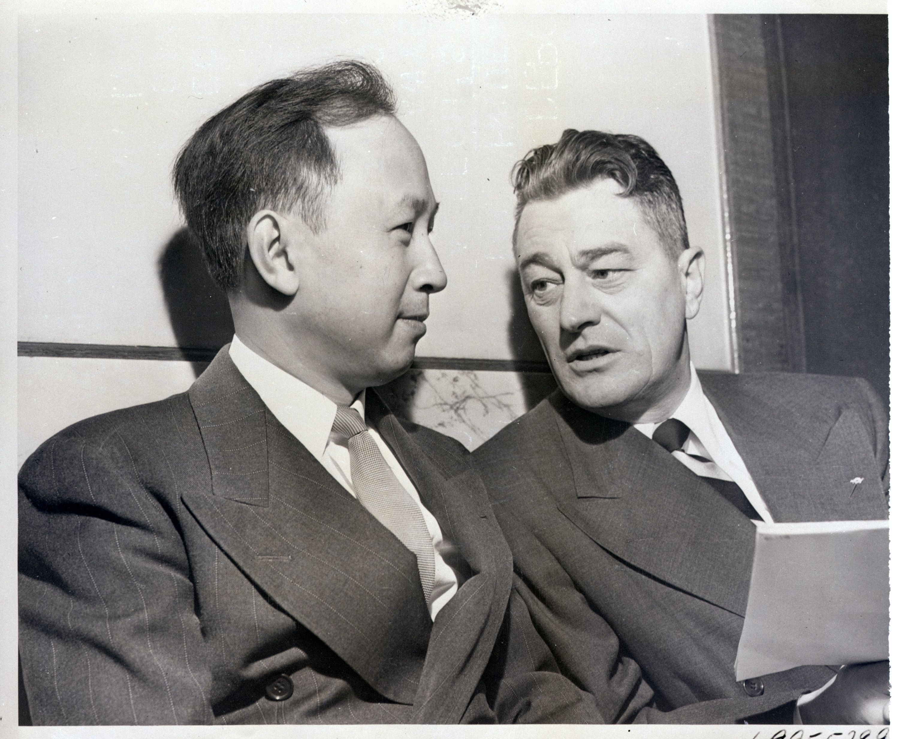 (Original Caption) 11/16/1950- Los Angeles, CA- Dr. Hsue-Shen Tsien (left), Director of Caltech's Jet Propulsion Center, confers with his lawyer, Grant B. Cooper, during his deportation hearing. The Government is charging that Dr. Tsien was a Communist when he entered the United States in 1935. He was arrested last September after a large shipment of technical matter was seized by immigration officials.