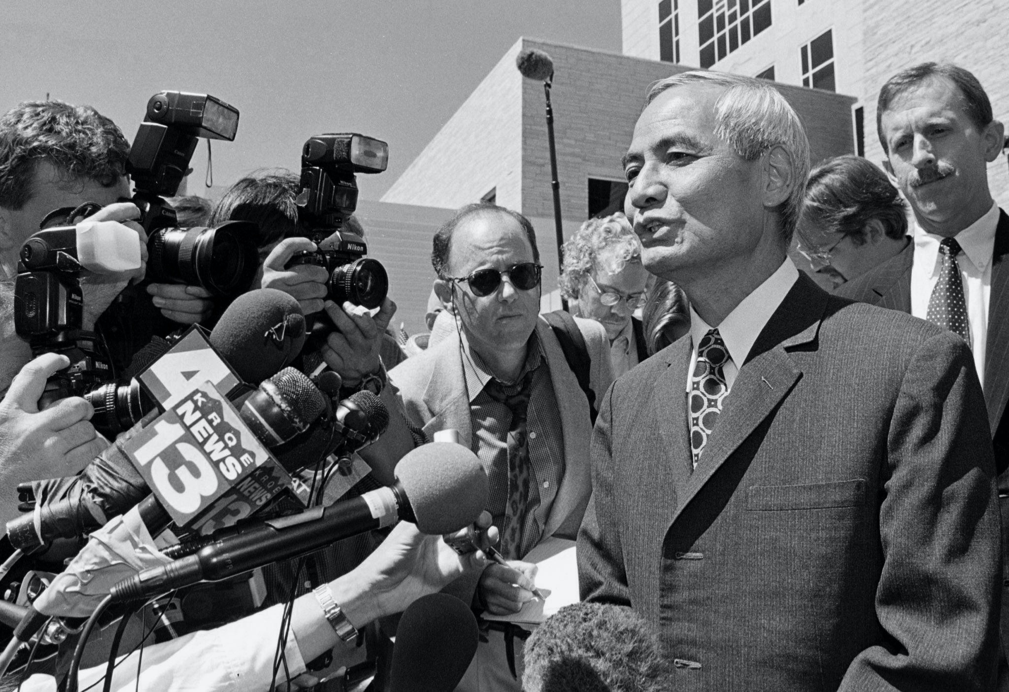 Former Los Alamos nuclear scientist Wen Ho Lee (R front) addresses the media outside the Federal Courthouse after he was freed from nine months of solitary confinement, 13 September 2000, in Albuquerque, New Mexico. US District Court Judge James Parker ordered the 60-year-old Taiwan-born scientist freed in a plea bargain in which Lee pleaded guilty to one felony count of downloading nuclear weapons design secrets to a non-secure computer at the Los Alamos laboratory.