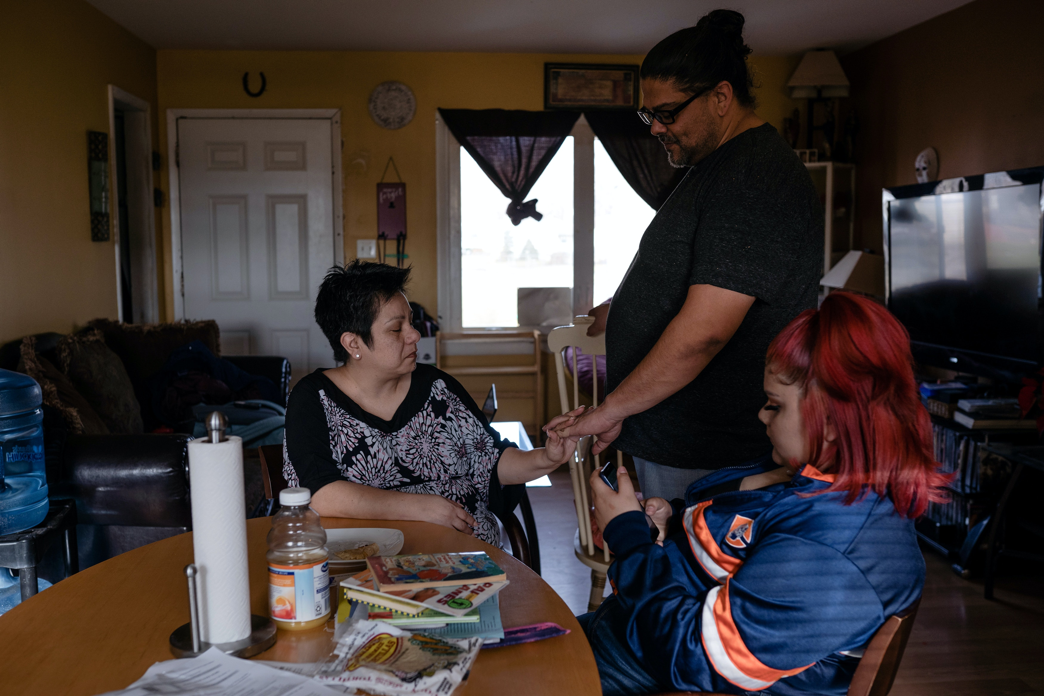 Angela Ramirez, who was diagnosed with breast cancer, and her husband Randy talk while their daughter Ada checks her phone in Waukegan, Ill. on Jan. 2, 2020. The Ramirezes live less than six miles away from two factories that emit ethylene oxide, a gas linked to cancer. Pat Nabong for The Intercept.
