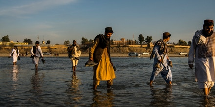 Friends cross the Helmand River in Helmand's capital Lashkar Gah, on foot, on the fourth day of a week-long reduction in violence (RIV) agreement between the Taliban, the Afghan government and U.S. forces in Afghanistan. The period has been marked by a relaxed atmosphere that has seen local residents out and about on streets that would ordinarily be all but abandoned.