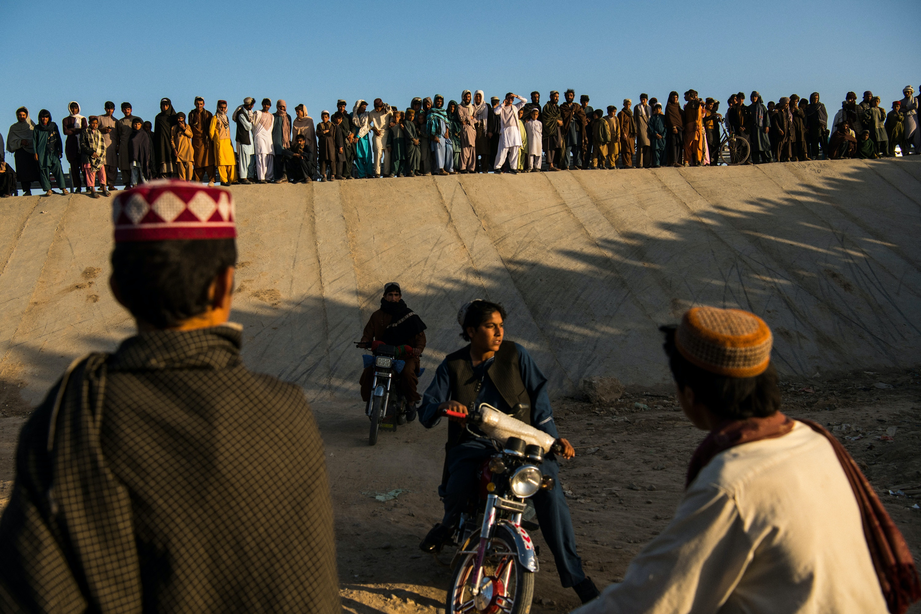 "On the final afternoon of a one-week partial ceasefire between the Taliban, the Afghan government, and U.S. forces, men and boys descended a bridge in Chah-e Anjir, outside Helmand's capital Lashkar Gah, to watch motorcyclists ride up its steep concrete embankment and perform tricks. When asked about the occasion, one onlooker, Omar, said ""It's Friday, and the last hours of the ceasefire."""