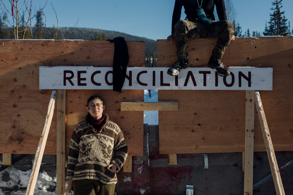 "Victoria Redsun and another supporter wait on the gate for police to enforce Coastal GasLink's injunction at Unist'ot'en Healing Centre near Houston, B.C. on Saturday, February 8, 2020. The word ""reconciliation"" is written across the gate to make the point that police, the government and Coastal GasLink would destroy it by forcing entry into Wet'suwet'en traditional territory. Amber Bracken"