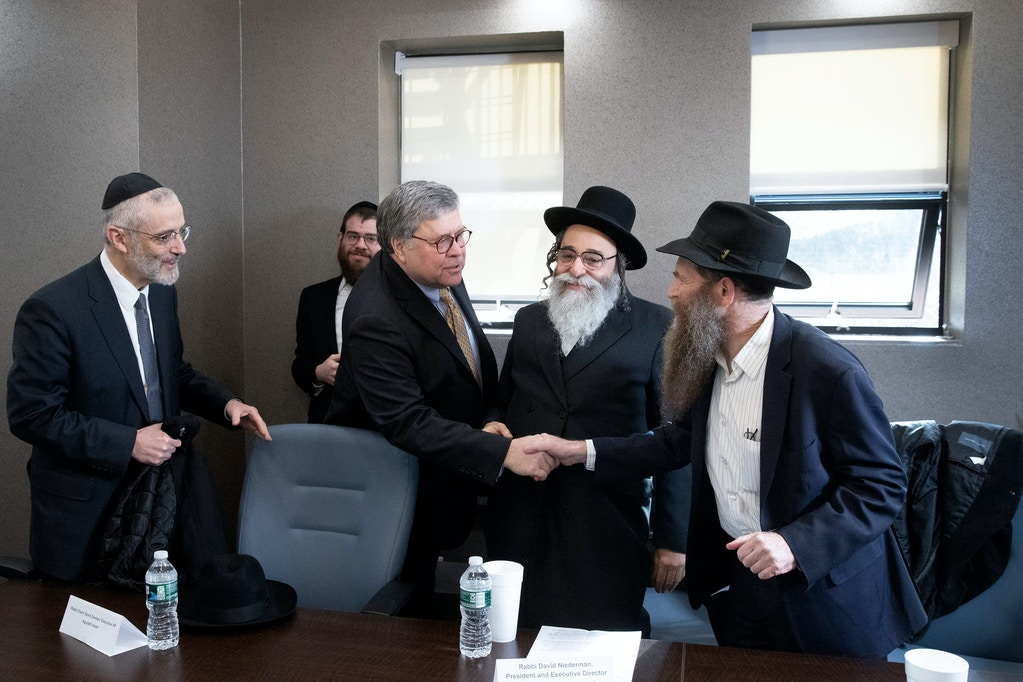 "Attorney General William Barr, center, shakes hands with Rabbi Eli Cohen, right, at a meeting with Jewish leaders at the Boro Park Jewish Community Council, Tuesday, Jan. 28, 2020 in New York. Rabbi Chaim David Zweibel, left, and Rabbi David Niederman, second from right, also took part in the meeting. Barr ordered federal prosecutors across the U.S. on Tuesday to step up their efforts to combat anti-Semitic hate crimes as he announced charges against a suspect who had slapped three Jewish women but was repeatedly released from jail under New York's bail reform laws. Barr said at the meeting in Brooklyn that he has been ""extremely distressed by the upsurge in violence"" in Jewish communities, including in New York City, which saw a string of anti-Semitic attacks during the Hanukkah holiday. (AP Photo/Mark Lennihan)"