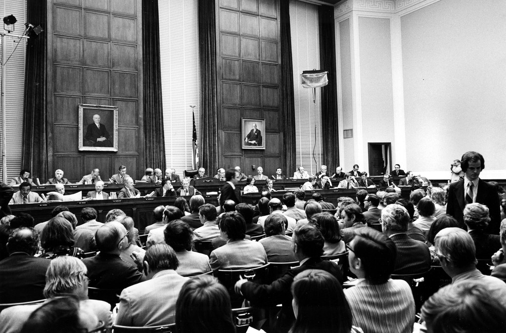Members of the U.S. House of Representatives Judiciary Committee, investigating grounds of impeachment of President Nixon, start Wednesday night's session on Capitol Hill in Washington, D.C., May 1, 1974.  Chairman of the committee Rep. Peter Rodino, D-N.J., is at center.  Spectators sit in foreground.  (AP Photo)