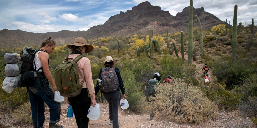 AJO, ARIZONA - MAY 10: Volunteers for the humanitarian aid organization No More Deaths walk with jugs of water for undocumented immigrants on May 10, 2019 near Ajo, Arizona. The volunteers distributed the aid along remote desert trails where immigrants pass after crossing the border from Mexico. The number of immigrant deaths, mostly due to dehydration and exposure, has risen as higher border security in urban border areas has pushed immigrant crossing routes into more remote desert regions. No More Deaths volunteer Scott Warren is scheduled to appear in federal court on May 29 in Tucson, charged by the U.S. government on two counts of harboring and one count of conspiracy for providing food, water, and beds to two Central American immigrants in January, 2018. If found guilty Warren could face up to 20 years in prison. The trial is seen as a watershed case by the Trump Administration, as it pressures humanitarian organizations working to reduce suffering and deaths of immigrants in remote areas along the border. The government claims the aid encourages human smuggling. In a separate misdemeanor case, federal prosecutors have charged Warren with abandonment of property, for distributing food and water along migrant trails.  (Photo by John Moore/Getty Images)