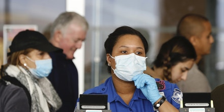 A Transportation Security Administration (TSA) employee adjusts her face mask in between screening passengers entering through a checkpoint at John F. Kennedy International Airport, Saturday, March 14, 2020, in New York.  White collar workers trying to avoid contagion during the viral pandemic can work from home or call in sick if they experience symptoms of the virus, but that's not an option for millions of other workers who routinely come into contact with the public. While tech companies have implemented work-from-home policies, only 29% of U.S. workers have that option, according to the Bureau of Labor Statistics. (AP Photo/Kathy Willens)