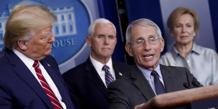 Anthony Fauci, director of the National Institute of Allergy and Infectious Diseases, speaks as U.S. President Donald Trump, left, listens during a Coronavirus Task Force news conference in the briefing room of the White House in Washington, D.C., U.S., on Friday, March 20, 2020. Americans will have to practice social distancing for at least several more weeks to mitigate U.S. cases of Covid-19, Fauci said today. Photographer: Al Drago/Bloomberg