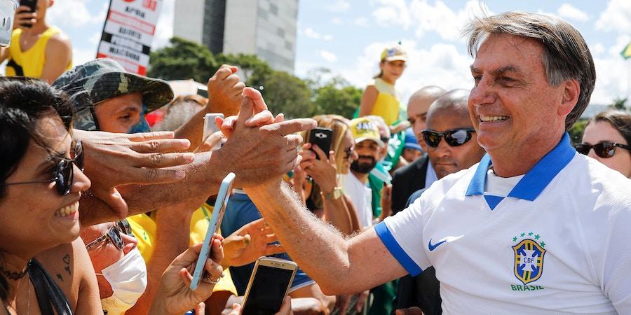 O presidente Jair Bolsonaro cumprimenta os apoiadores que se reuniram em frente ao Palácio do Planalto no domingo, dia 15 de março.