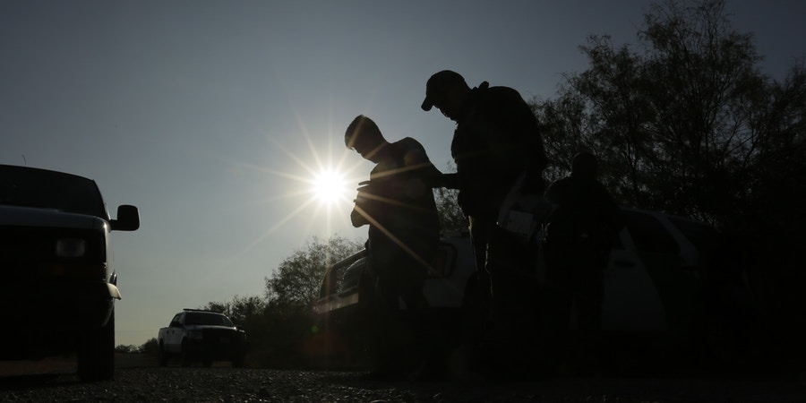 In this Wednesday, Nov. 6, 2019, photo, Border Patrol agents stop men thought to have entered the country illegally, near McAllen, Texas, along the U.S.-Mexico border. In the Rio Grande Valley, the southernmost point of Texas and historically the busiest section for border crossings, the U.S. Border Patrol is apprehending around 300 people daily, down from as many as 2,000 people a day in May. (AP Photo/Eric Gay)