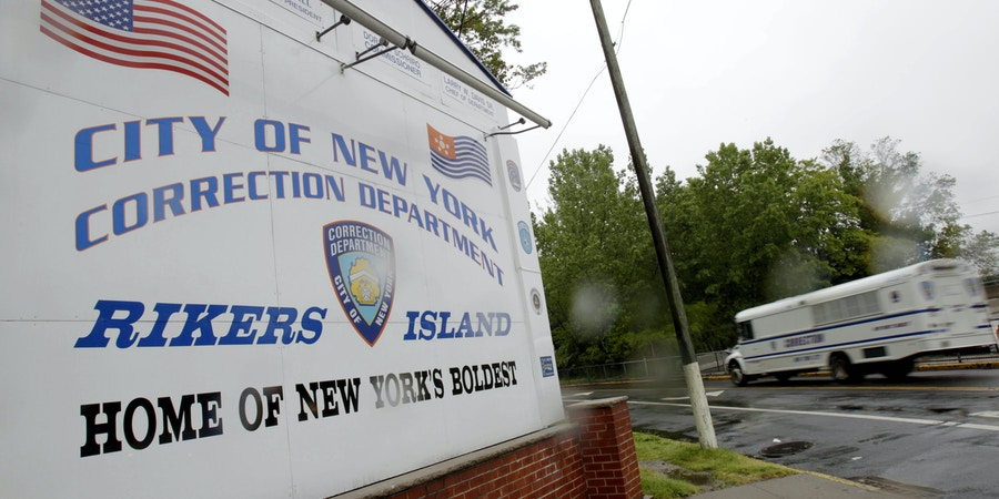 FILE - In this May 17, 2011  file photo, a New York City Department of Corrections bus passes the sign near the gate at the Rikers Island jail complex in New York.  Four correctional officers at Rikers Island jail have been suspended without pay after they allegedly stood by and failed to stop a teenage inmate from hanging himself on Thanksgiving, leaving him hospitalized in intensive care. Nicholas Feliciano, 18, remained unconscious in a hospital prison ward Wednesday, Dec. 4, 2019 a week after he nearly died in his Rikers Island jail cell, according to the Legal Aid Society, the public defender organization that represents him in court.  (AP Photo/Seth Wenig, File)