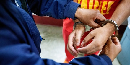 A detainee is cuffed for medical transport at the Stewart Detention Center, Friday, Nov. 15, 2019, in Lumpkin, Ga. The Stewart Detention Center sits in Lumpkin, a rural town about 140 miles southwest of Atlanta and right next to the Georgia-Alabama state line. The city's 1,172 residents are outnumbered by the roughly 1,650 male detainees that U.S. Immigration and Customs Enforcement said were being held in the detention center in late November. (AP Photo/David Goldman)