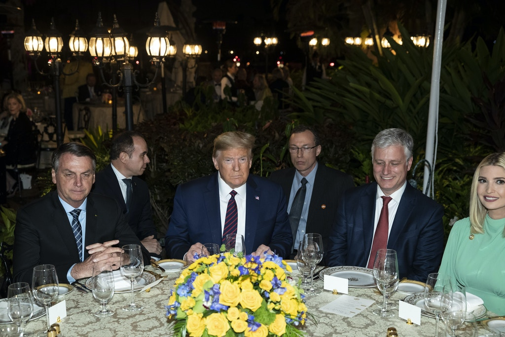 President Donald Trump is seated before a dinner with Brazilian President Jair Bolsonaro, left, National Security Adviser Robert O'Brien, and Ivanka Trump, the daughter and assistant to President Donald Trump, at Mar-a-Lago, Saturday, March 7, 2020, in Palm Beach, Fla. (AP Photo/Alex Brandon)