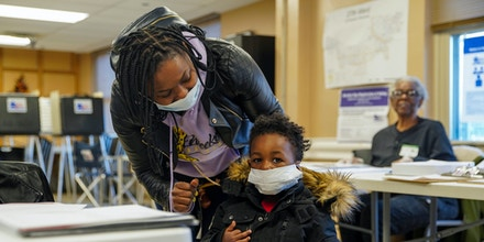 Nikolette Baxter, 30, and son Jeremy, 2, both of the West Side of Chicago, wear masks when she came to vote at Midwest Terrace senior apartments which handled voting for the 50th precinct in the 27th ward. (Annie Costabile/Chicago Sun-Times via AP)