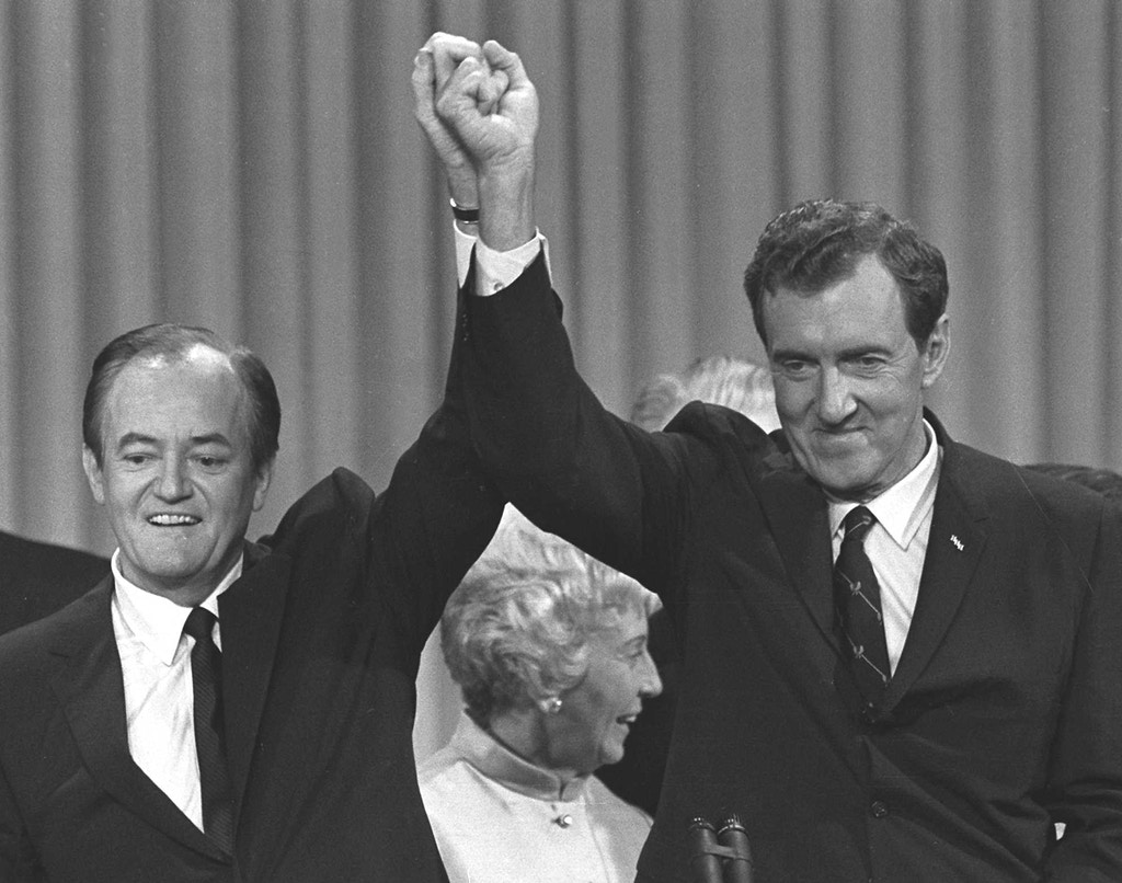 Hubert H. Humphrey, left, and his running mate, Sen. Edmund S. Muskie, stand before Democratic National Convention delegates with hands clasped on Aug. 29, 1968. (AP Photo)