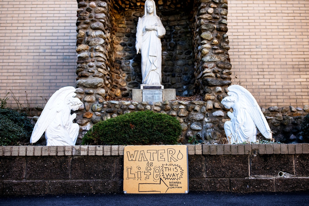 "NEWARK, NJ. - FEBRUARY 22, 2020: A ""Water is Life"" sign outside of the water distribution center in St. Lucy's Rectory Church in Newark, NJ."